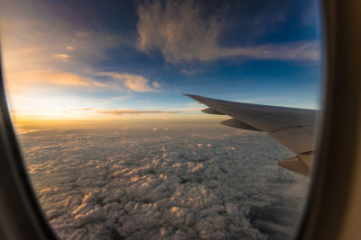 The view from an airplane window of clouds and the plane's wing.